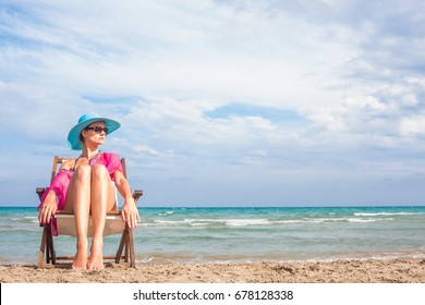 Woman sitting on a deck chair at the beach