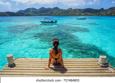 Woman sitting on the deck in Crab Cay (Cayo Cangrejo), Providence Island (Isla de Providencia), Colombia