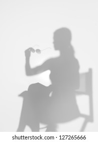 woman sitting on director's chair reading a book with sunglasses in her hand, behind a diffuse surface