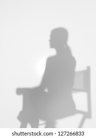 woman sitting on a director's chair, behind a diffuse surface, back lit
