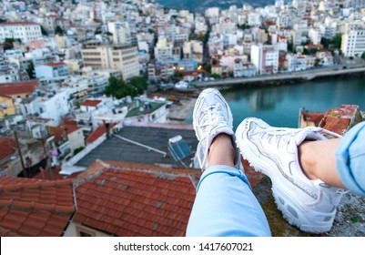 Woman sitting on the edge of building and her legs with white sneakers dangling against red rooftops and cityscape