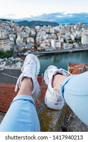 Woman sitting on the edge of building and her legs with white sneakers dangling against red rooftops,cityscape and sea