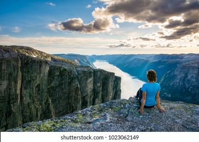 A woman is sitting on the edge of cliff on the way to boulder (Kjeragbolten) stuck in between the mountain crevices of Kjerag above a fjord, near Lysebotn, Norway. The feeling of complete freedom