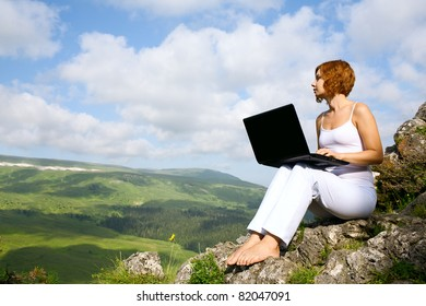 woman sitting on the edge of a cliff with a laptop