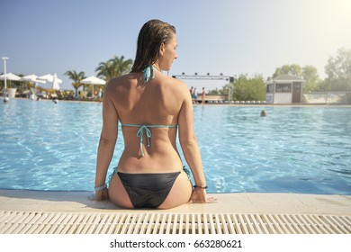 Woman sitting on the edge of the pool