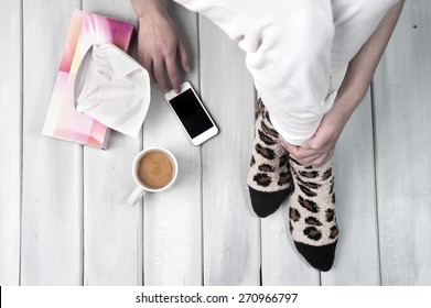 Woman sitting on floor with coffee smartphone and tissue box next to her