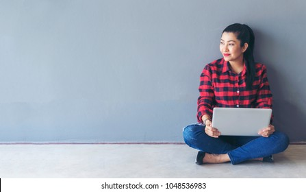 Woman sitting on floor with computer laptop, think about creating project diversity and professional teamwork collaboration. Typing keyboard for keeping note or memo topic before meeting with manager.