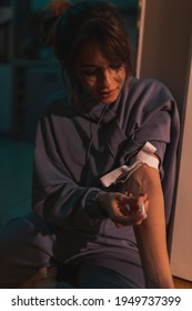 Woman sitting on the floor in the dark shooting up with heroin; female drug addict injecting herself with heroin dose intravenously; drug addiction and substance abuse concept