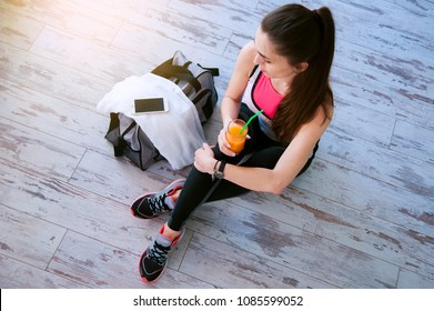 Woman with sitting on the floor with glass of orange juice after sport