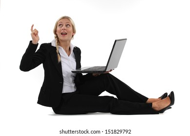 woman sitting on the floor with her laptop and having a great idea