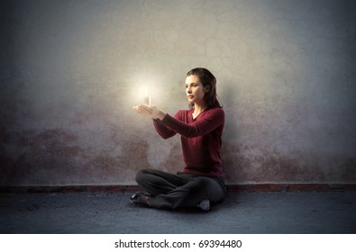 Woman sitting on the floor and holding a candle