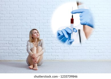 Woman sitting on the floor and looking on imaginary syringe. Fear of doctors and injections concept.