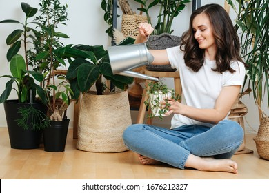 A woman sitting on the floor pours water into a flower pot, she cares for house plants