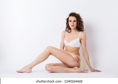 Woman sitting on the floor in the studio isolated. Young sports girl a beautiful healthy body.