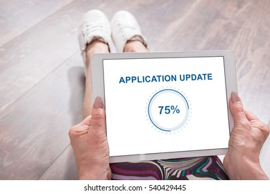 Woman sitting on the floor with a tablet showing application update concept
