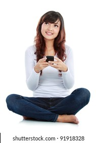 Woman sitting on floor and text messaging on a mobile phone while thinking what to say. isolated over white background