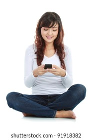 Woman sitting on floor and text messaging on a mobile phone isolated over white background