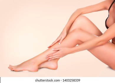 Woman sitting on the floor and touching her leg by hands, Beauty and skin care concept