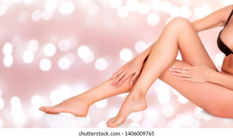 Woman sitting on the floor and touching her leg by hands, Beauty and skin care concept. Abstract background with blurred lights