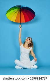 woman sitting on the floor with an umbrella on a blue background