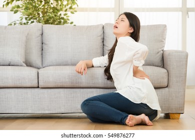 Woman sitting on floor while touching her back in living room. lifestyle and health concept. mixed race asian chinese model.