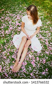Woman sitting on the grass covered with pink cherry tree petals and flowers, closeup of legs