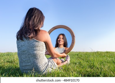 Woman sitting on grass looking at  her mirror image