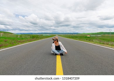 A woman is sitting on the grassland highway under the blue sky and white clouds.