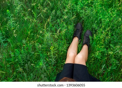 woman sitting on green grass top view