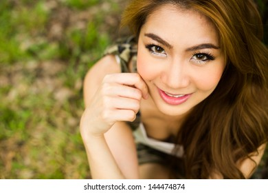 Woman sitting on  the green grass in the park