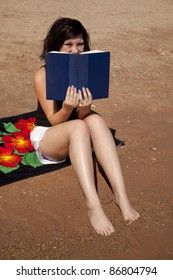 A woman sitting on her beach towel peeking over the top of her book.