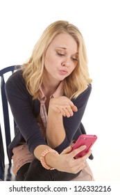 A woman sitting on her chair blowing a kiss at her cell phone for a picture.