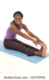 a woman sitting on her mat stretching out her legs with a smile on her face.