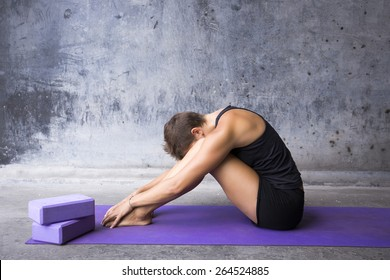 Woman sitting on her mat hiding her face between her legs. Finding refuge in yoga practice.