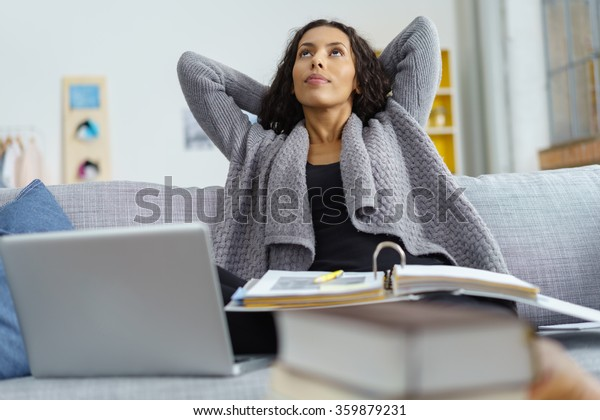 woman sitting on her sofa with a pile of books and a laptop, looking up with her hands behind her head