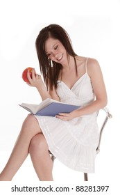 a woman sitting on her stool reading a book and holding a piece of fruit with  a smile on her face.