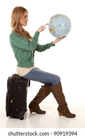 A woman sitting on her suitcase holding on to a world globe pointing out where she wants to go.