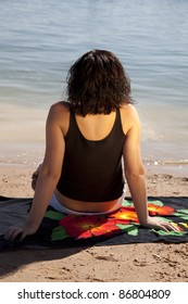 A woman sitting on her towel showing her back.