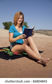 a woman sitting on her towel at the beach reading.