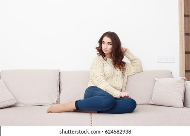 woman sitting on her white sofa in white pullover