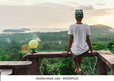 Woman sitting on the high overlooking the island at sunrise, koh Phangan, Thailand