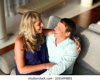 Woman sitting on the lap of man and they both smile.