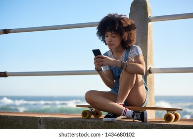 Woman sitting on longboard using her mobile cell phone by the ocean at sunset