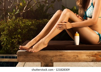 Woman sitting on lounge and moisturizing her skin