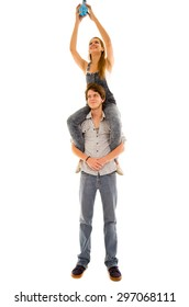 Woman sitting on mans shoulders while she assembles a blue lightbulb high up and he looks forward with careful smile.