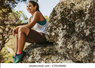Woman sitting on mountain looking away and smiling. Female mountain climber looking at the view and smiling.