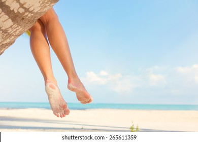 Woman sitting on palm tree at tropical beach