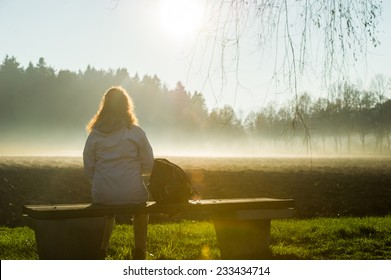 Woman sitting on a park bench overlooking a foggy field while beeing illuminated by the sun.