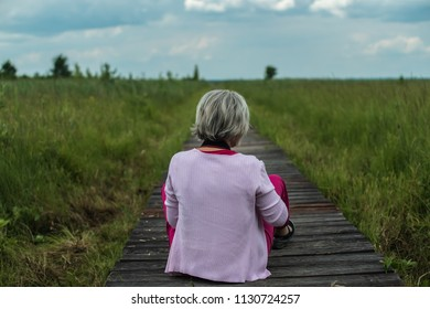 Woman sitting on the path made of planks in Biebrza Natural Reserve Park