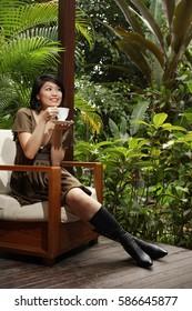 Woman sitting on patio, having cup of tea